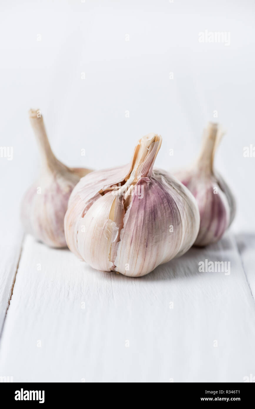 ripe garlic heads on white rustic table - Stock Image