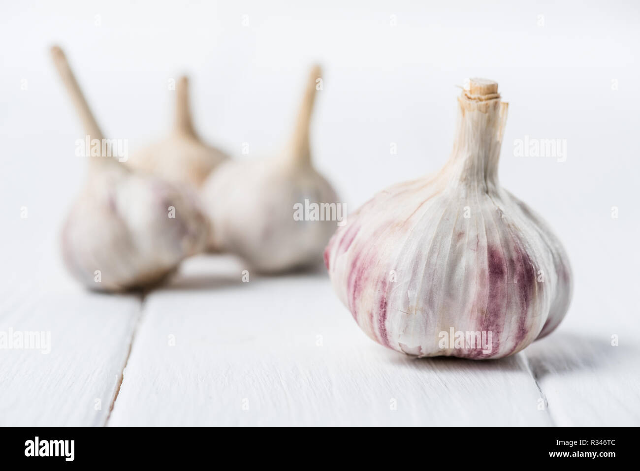 Ripe garlic bulbs on white wooden table - Stock Image