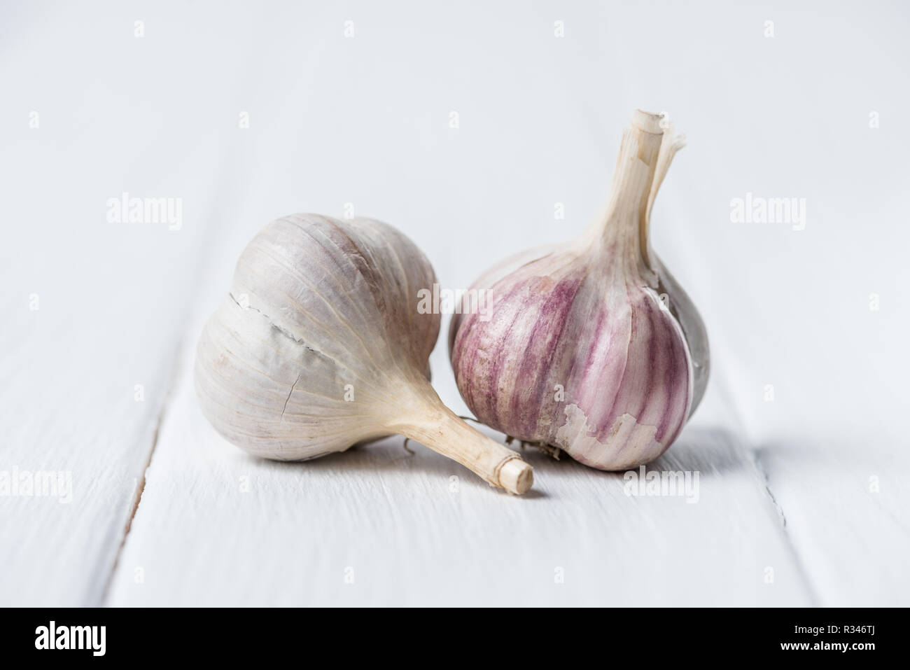 Two garlic heads on white wooden table - Stock Image