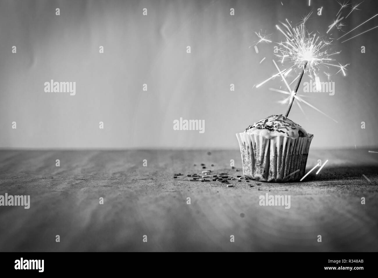 Cupcake with burning sparkler and copy space for congratulations - Stock Image