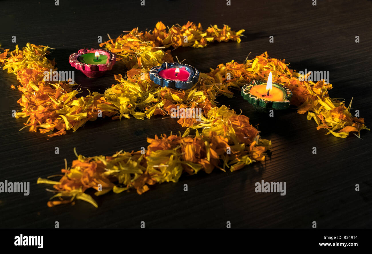 Illuminated diya placed on yellow flowers for celebrating diwali and dhanteras festival in India Stock Photo