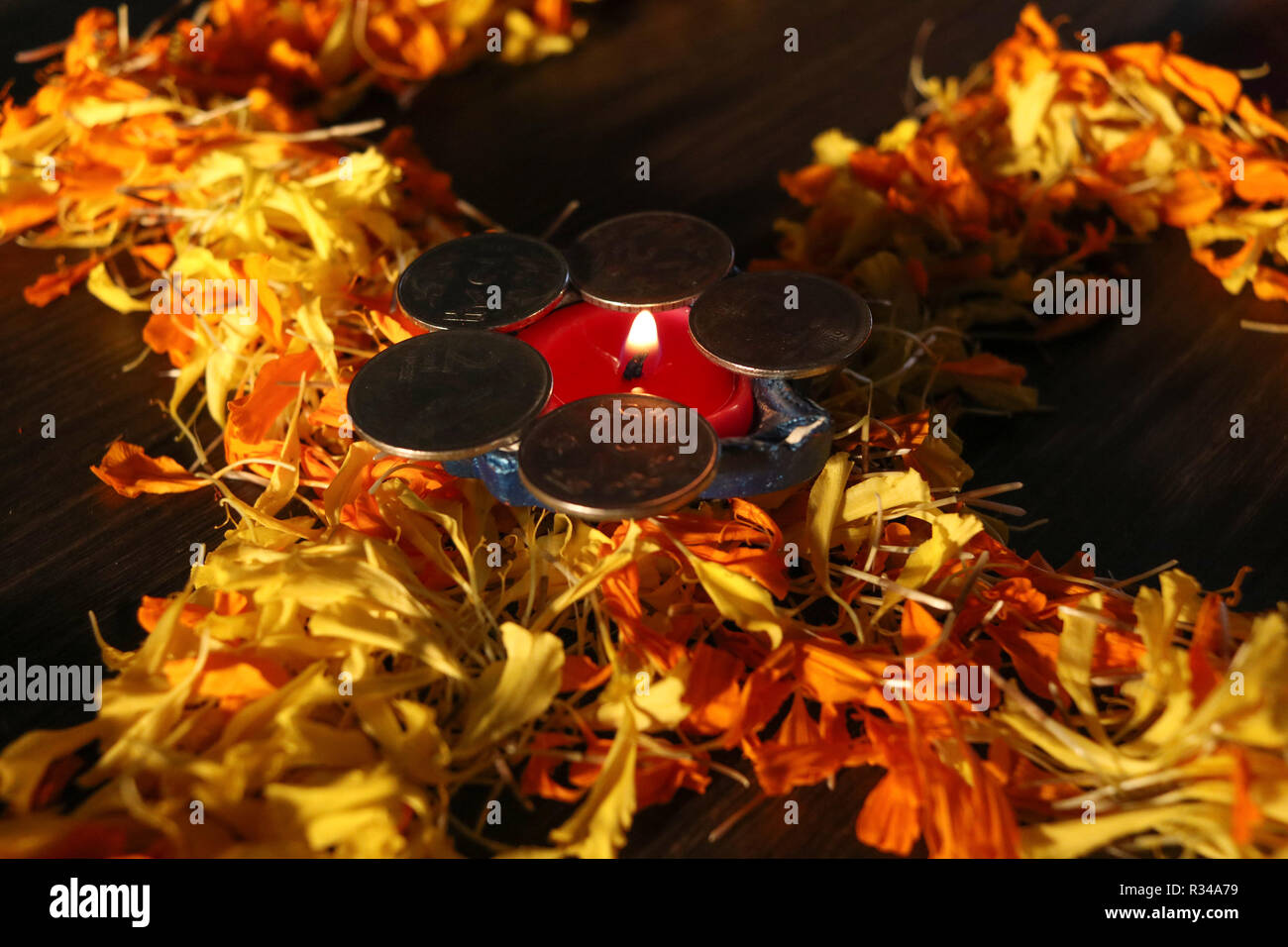 Lit diya placed on flower with coins for celebrating diwali and dhanteras festival in India Stock Photo