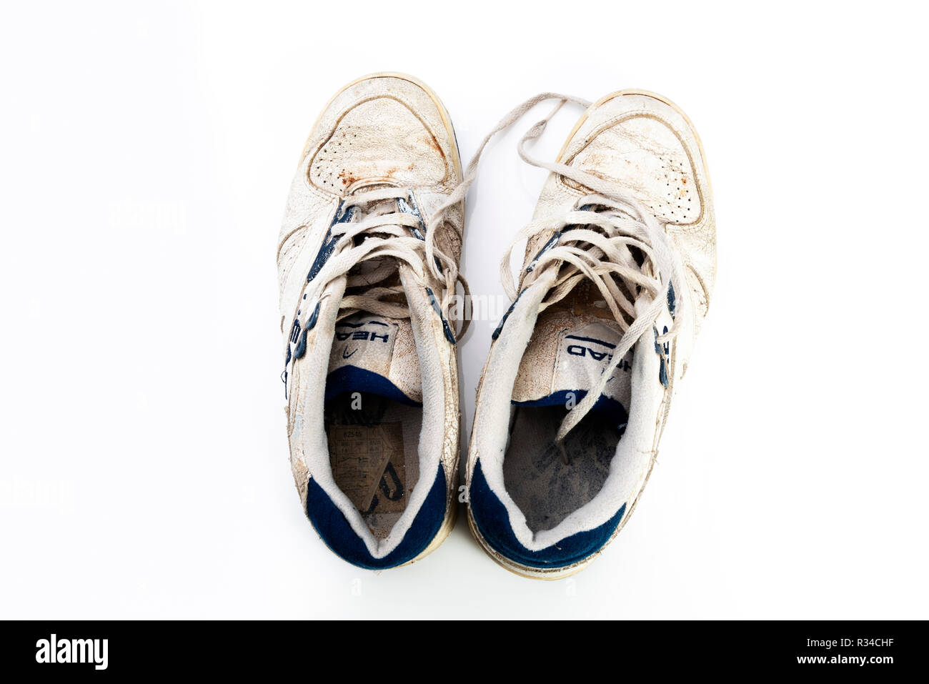 Pair of retro dirty old trainers. Worn and battered sneakers. - Stock Image