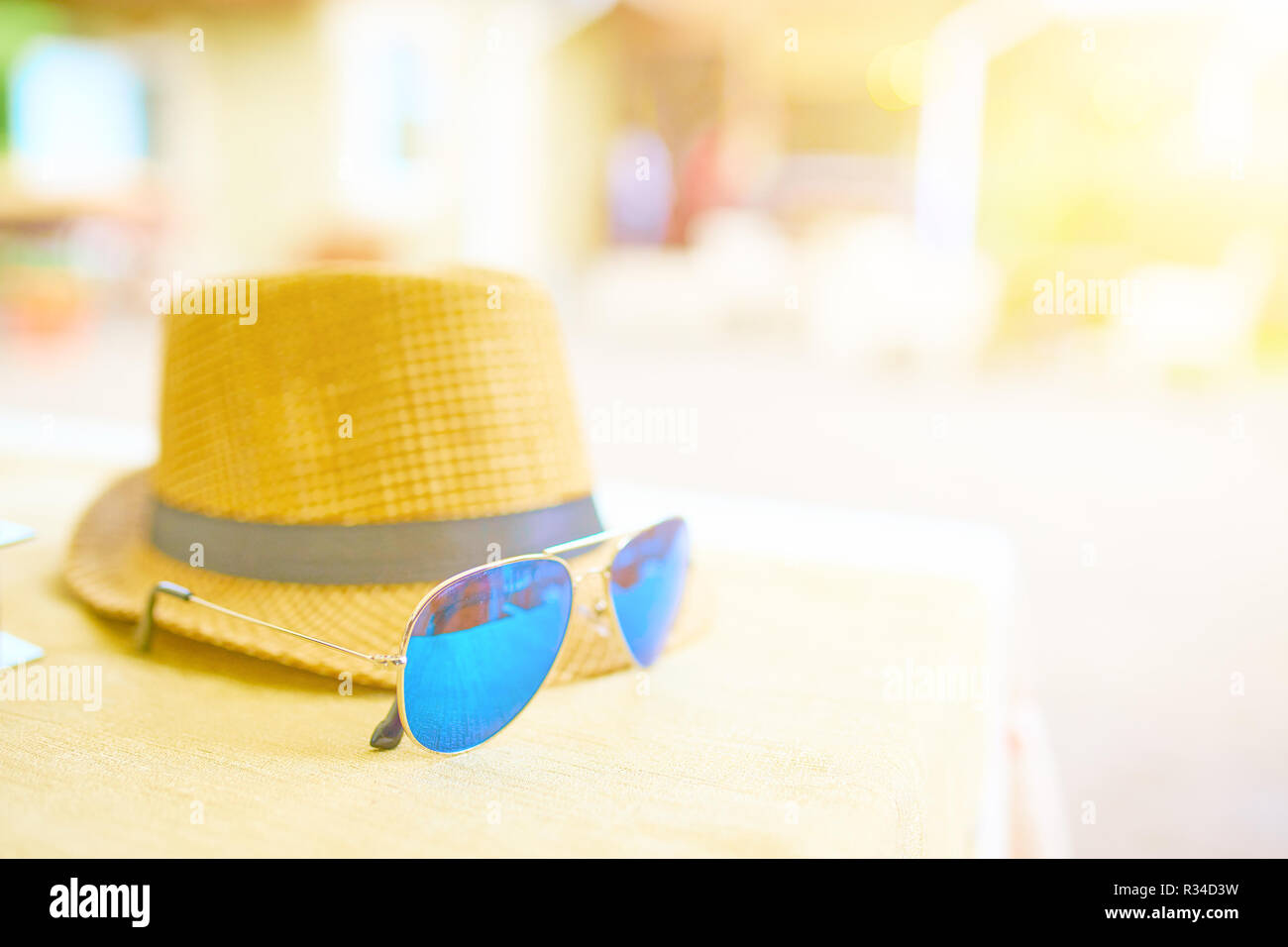 Straw hat and blue sunglasses on a hot day off on the table. Vacation concept - Stock Image