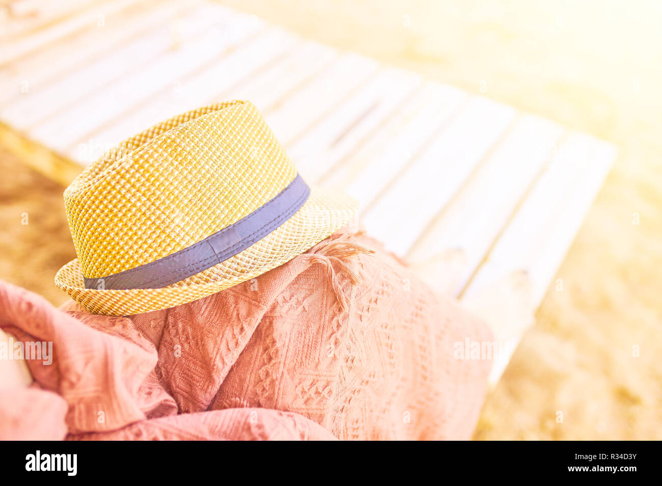 Person lying on a sunbed with a blanket and a beach hat. Straw hat on a hot day off. - Stock Image