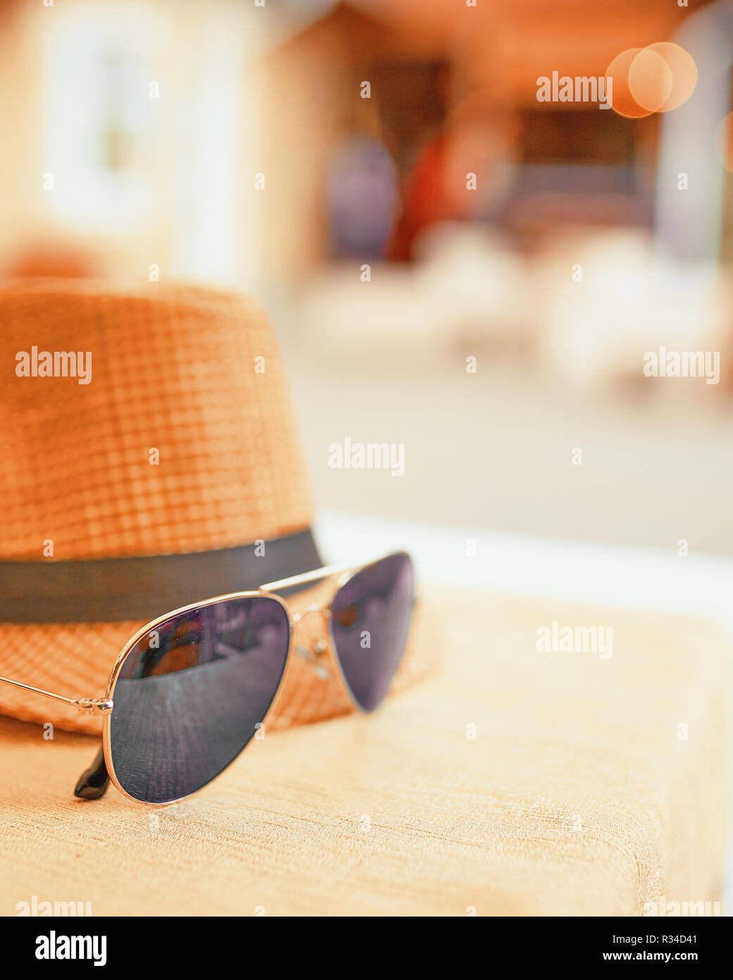Hat and dark sunglasses on a hot day off on the table. Resort concept - Stock Image