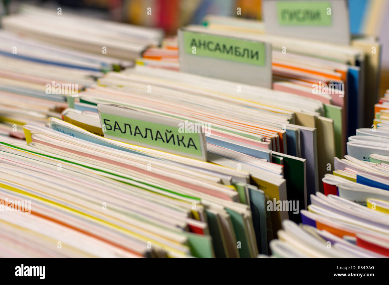 Edges of the multi-colored musical notebooks put in a row with the inscriptions in Russian 'balalaika' and 'ensembles' on a blurred background. - Stock Image
