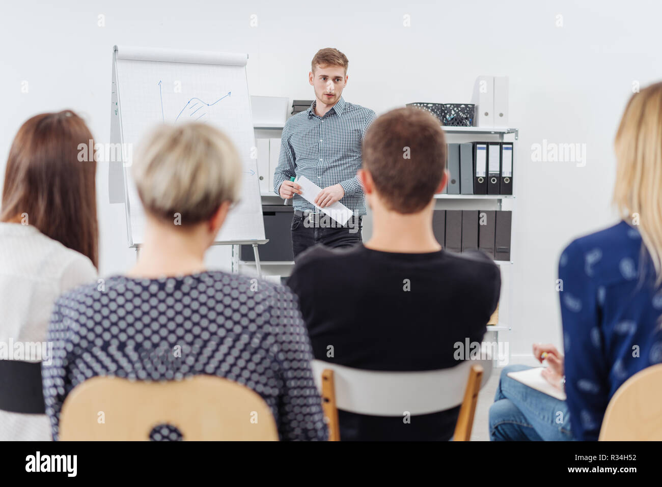 Businessman giving a presentation or in house training to a group of people viewed from behind with focus to the back of one guys head - Stock Image