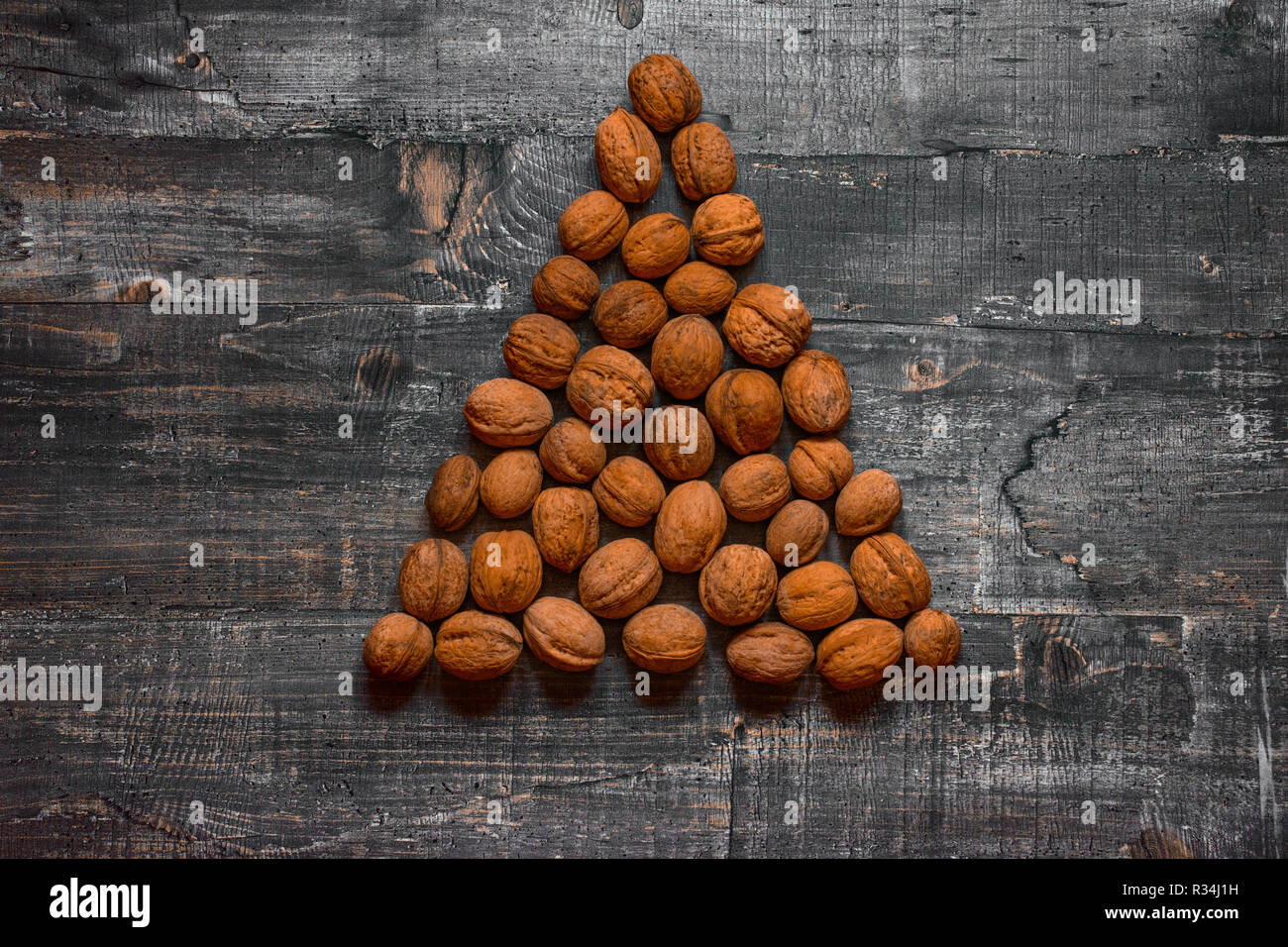 A few walnuts on an old wooden table or wooden surface are laid out in the shape of a Christmas tree. Concept flat Layout top view - Stock Image