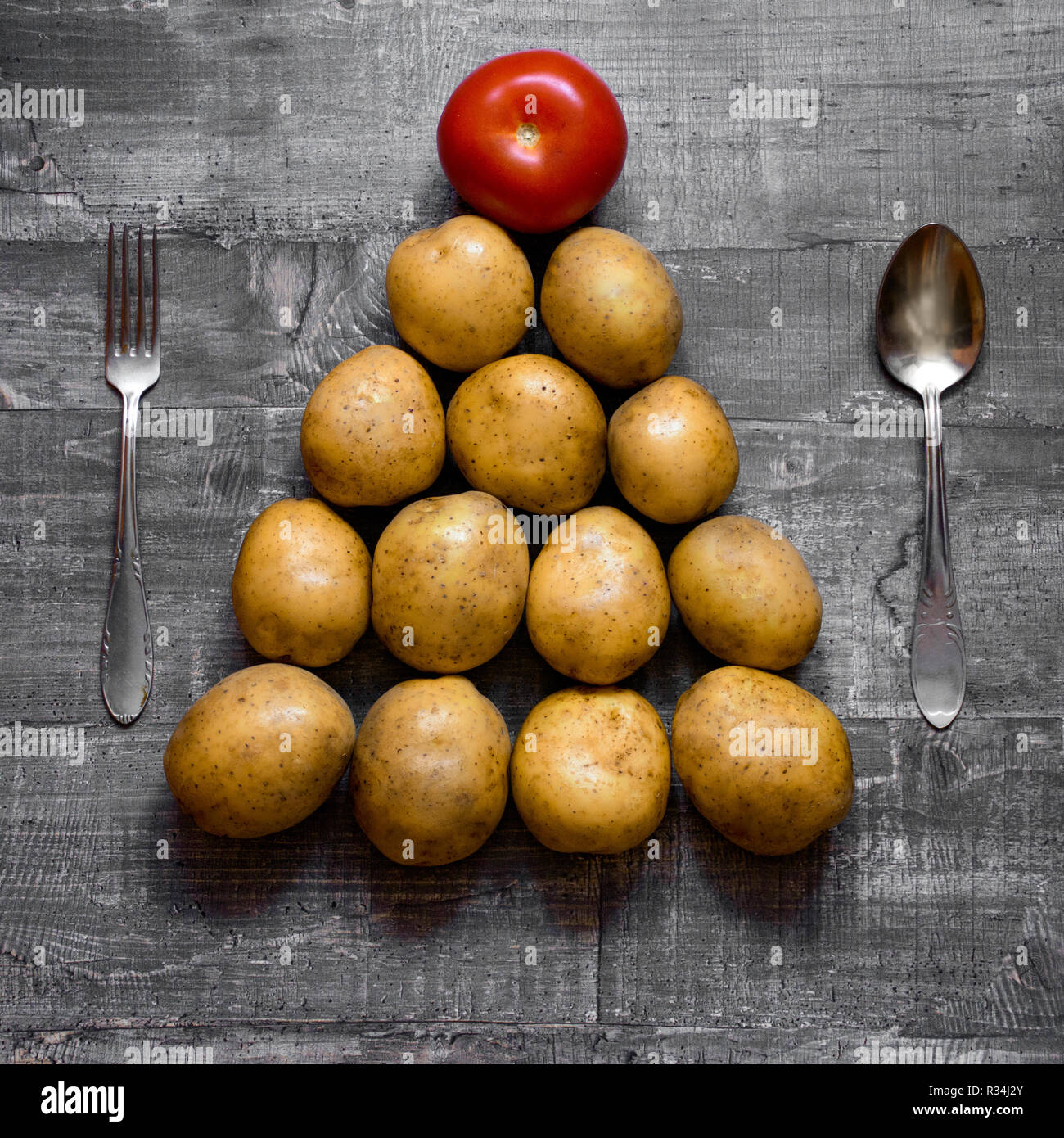 Concept potatoes and a tomato on an old wooden table or wooden surface is laid out in the shape of a Christmas tree. Flat Layout top view - Stock Image
