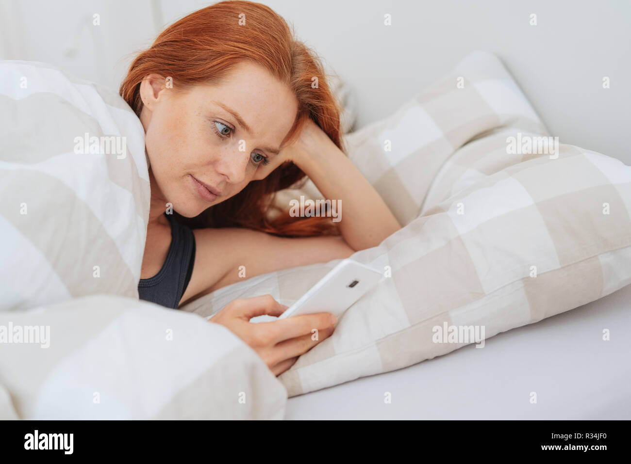 Attractive Redhead Woman Using A Mobile In Bed Lying Propped Up On