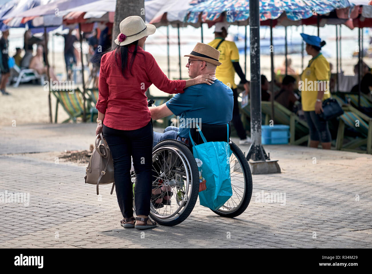 Disabled man in a wheelchair with supportive wife - Stock Image