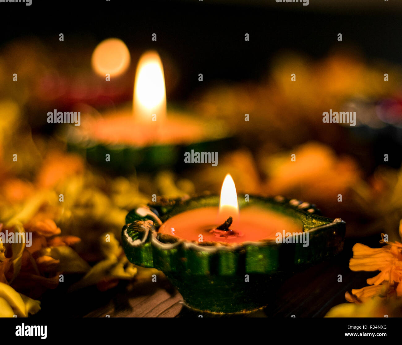 Illuminated diya paced with flowers for celebrating diwali and dhanteras in Asia Stock Photo