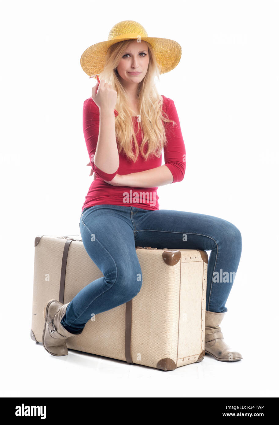 woman sitting on suitcase - Stock Image