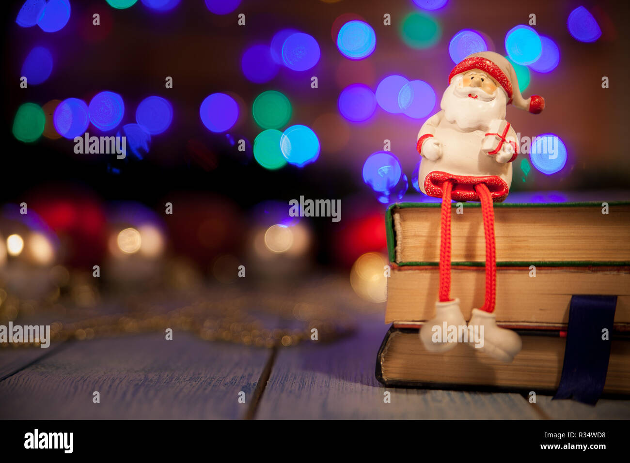 Toy Santa Klaus with a gift sits on the books on the background bokeh Stock Photo