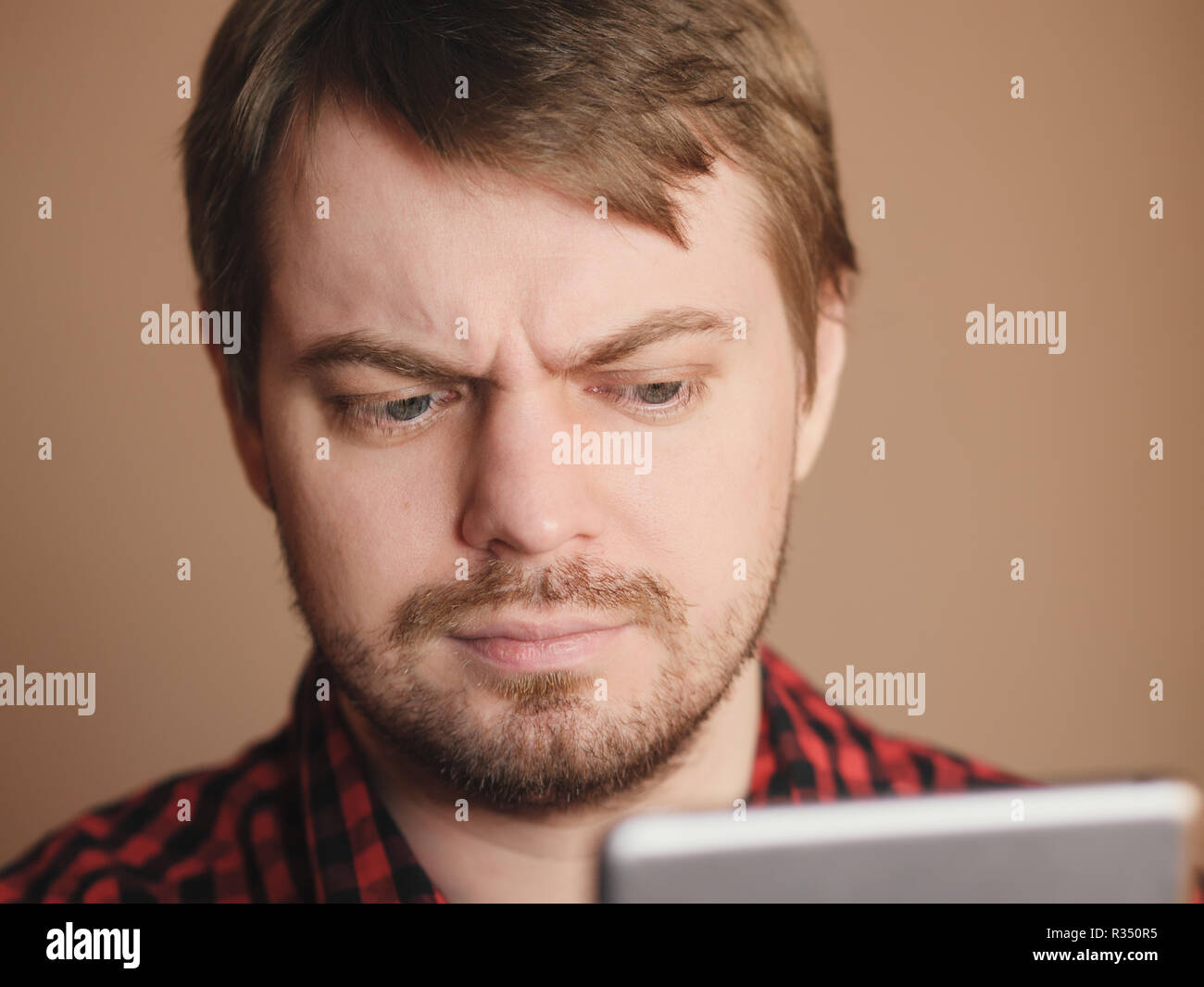 Young emotional man, looking down at pda on beige background. - Stock Image