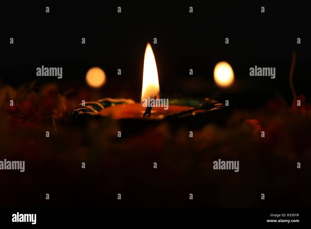 Lit diya placed on flowers for celebrating diwali and dhanteras Stock Photo