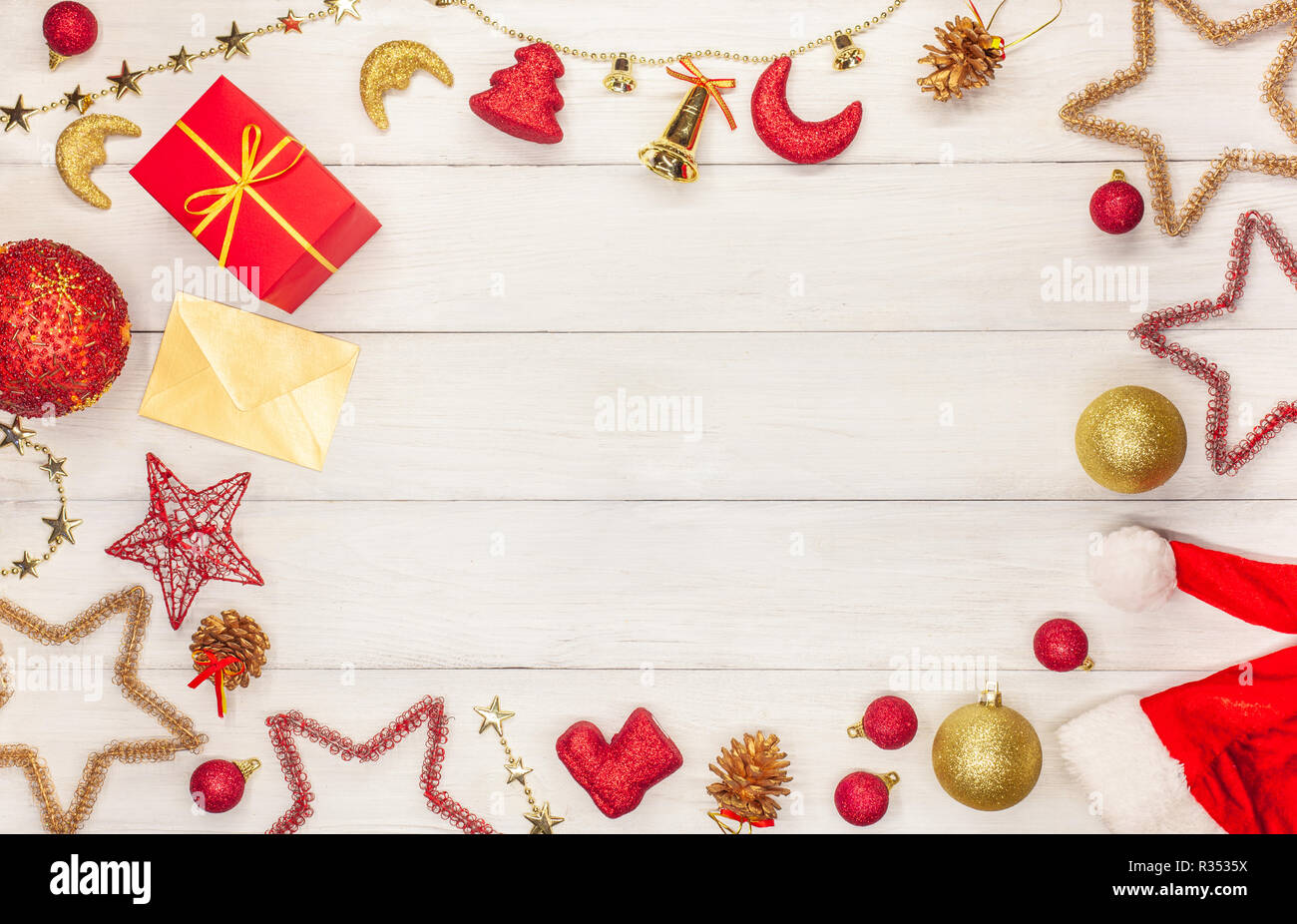 Christmas star toys, balls, bells, Christmas bells, asterisks, a box with a gift and a gold envelope on a white wooden table - Stock Image