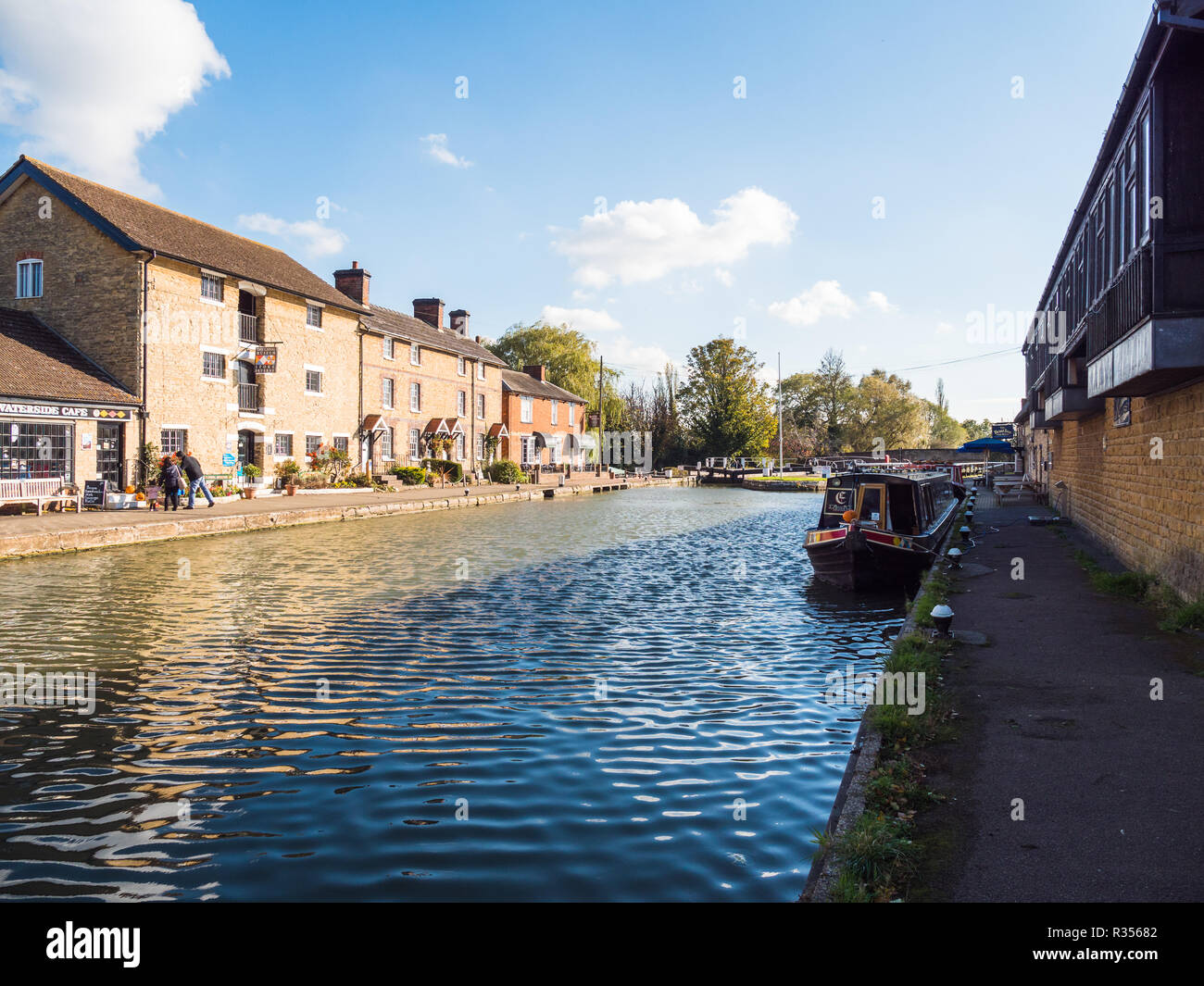 Stoke Bruerne UK October 31 2018: canal river with moored boats and shop around it in village in northamptonshire, england. - Stock Image