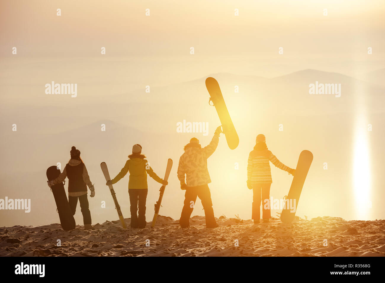 Group of skiers and snowboarders at sunset. Ski resort concept Stock Photo