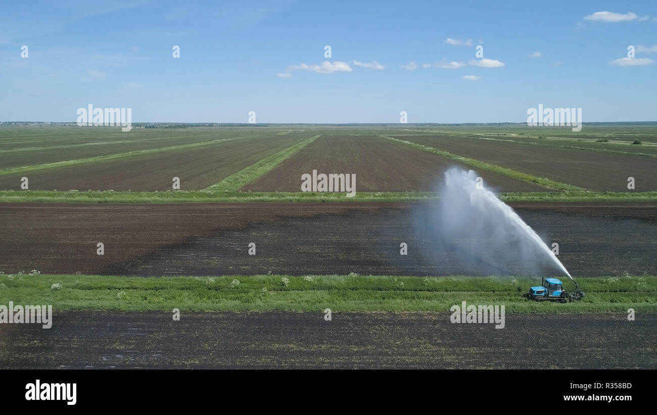 Aerial view of Crop Irrigation using the center pivot sprinkler system. An irrigation pivot watering agricultural land. Irrigation system watering farm land. - Stock Image