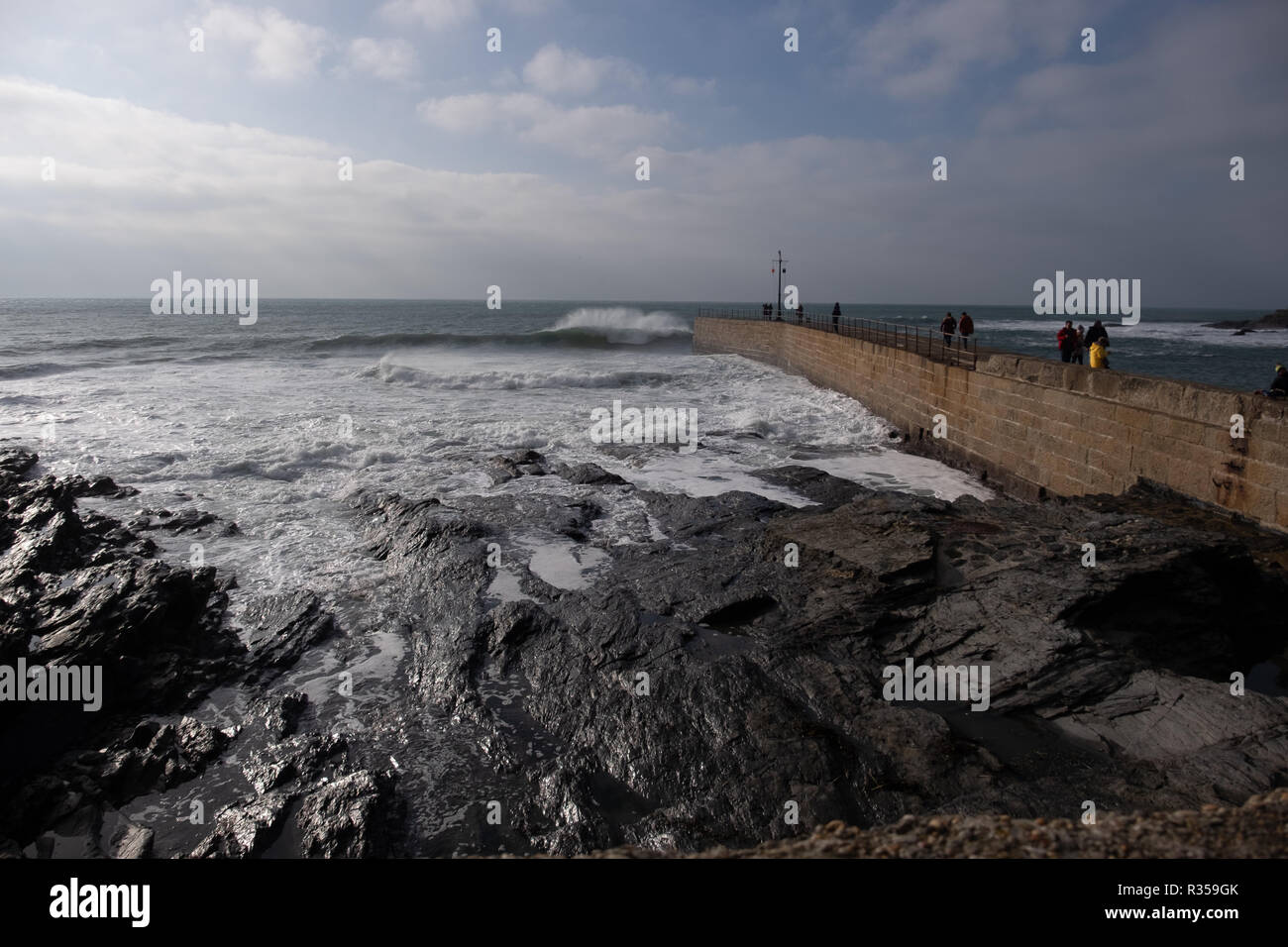 Wide angled view of people on the harbour wall watching the amazing waves powering in to break on the rocky shore of Porthleven, Cornwall. - Stock Image