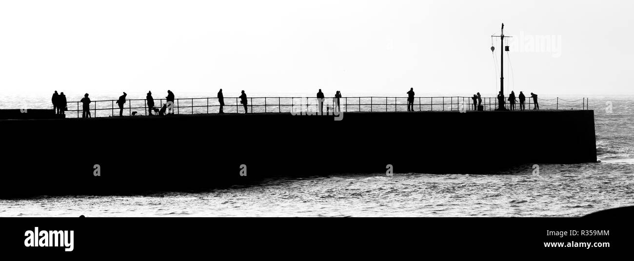 Black and white panoramic image of the harbour wall at Portreath with several people spread along the length looking at the seas beyond. - Stock Image