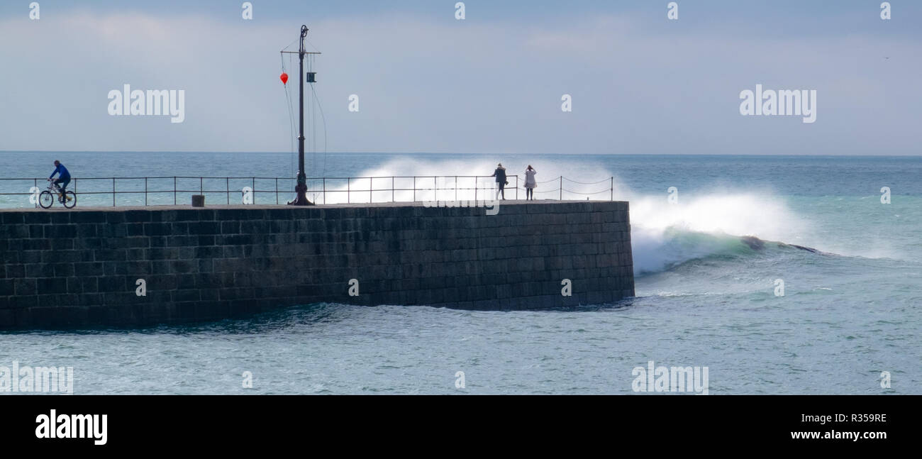 Rough seas hitting the harbour wall at Porthleven, Cornwall and soaking the onlookers in big waves. - Stock Image