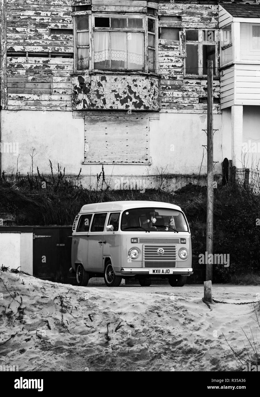 Vintage VW camper parked up in front of an old bay windowed, two storey building near the seafront of Portreath. - Stock Image