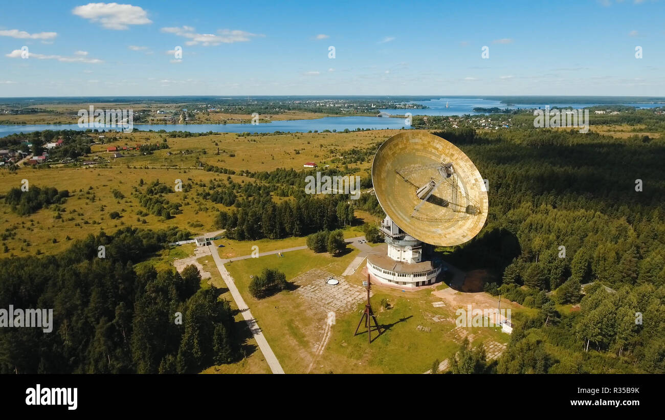 Radio astronomy observatory located in the forest. Aerial view Giant radio telescop, Large satellite dish.drone footage. Stock Photo