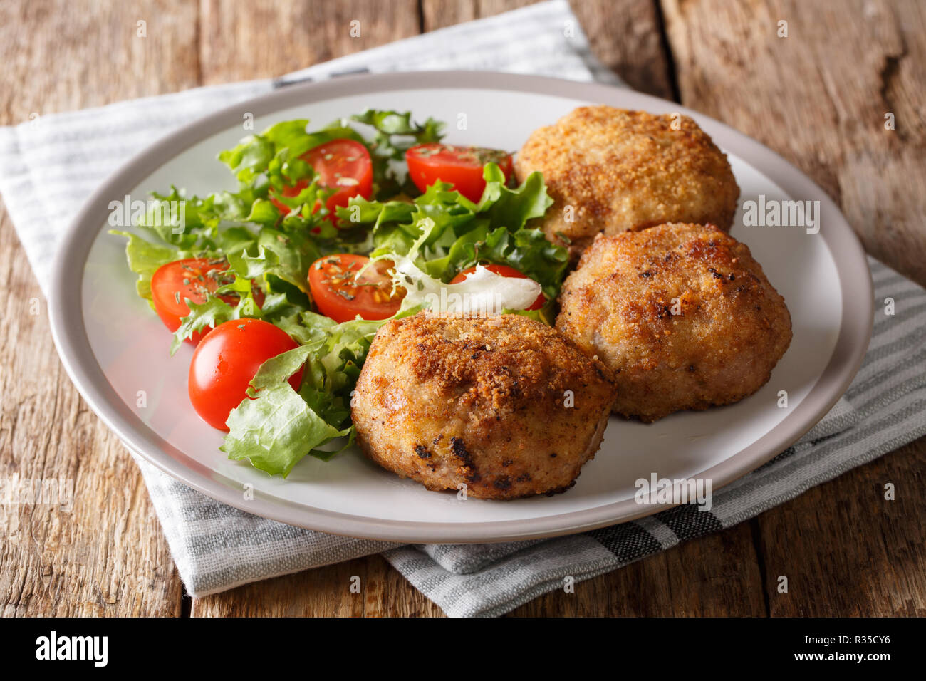 KarbonaderBreaded Pork PattyRecipe with fresh vegetable salad close-up on a plate on the table. Horizontal - Stock Image