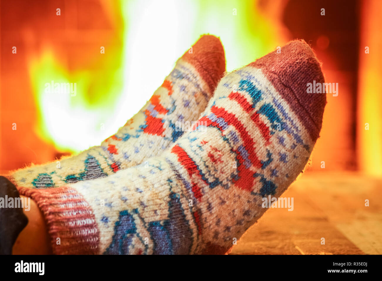 Man's Feet in lovely wool socks before cozy fireplace, in country house, winter vacation , horisontal. - Stock Image