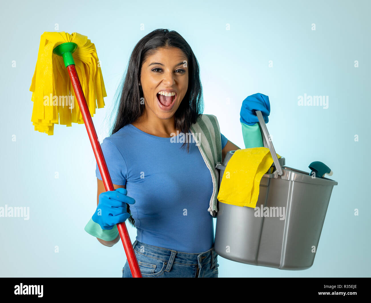 Beautiful happy latin woman holding cleaning equipment in Cleaning service Professional, housemaid and housework isolated on blue background. - Stock Image
