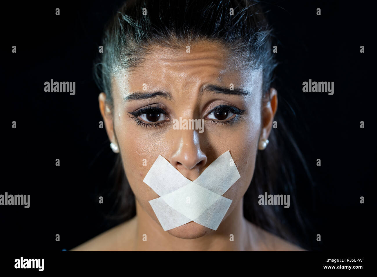 Attractive scared woman with taped mouth making in Silence Abuse Censorship Me too and Freedom of speech Concept Isolated on black background. - Stock Image