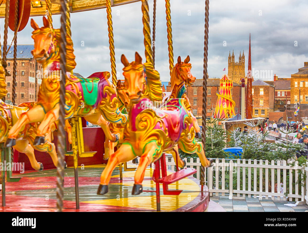 Merry go round carousel fairground ride at Gloucester Quays Victorian Christmas Market with tower of Gloucester Cathedral, Gloucester. hdr effect Stock Photo