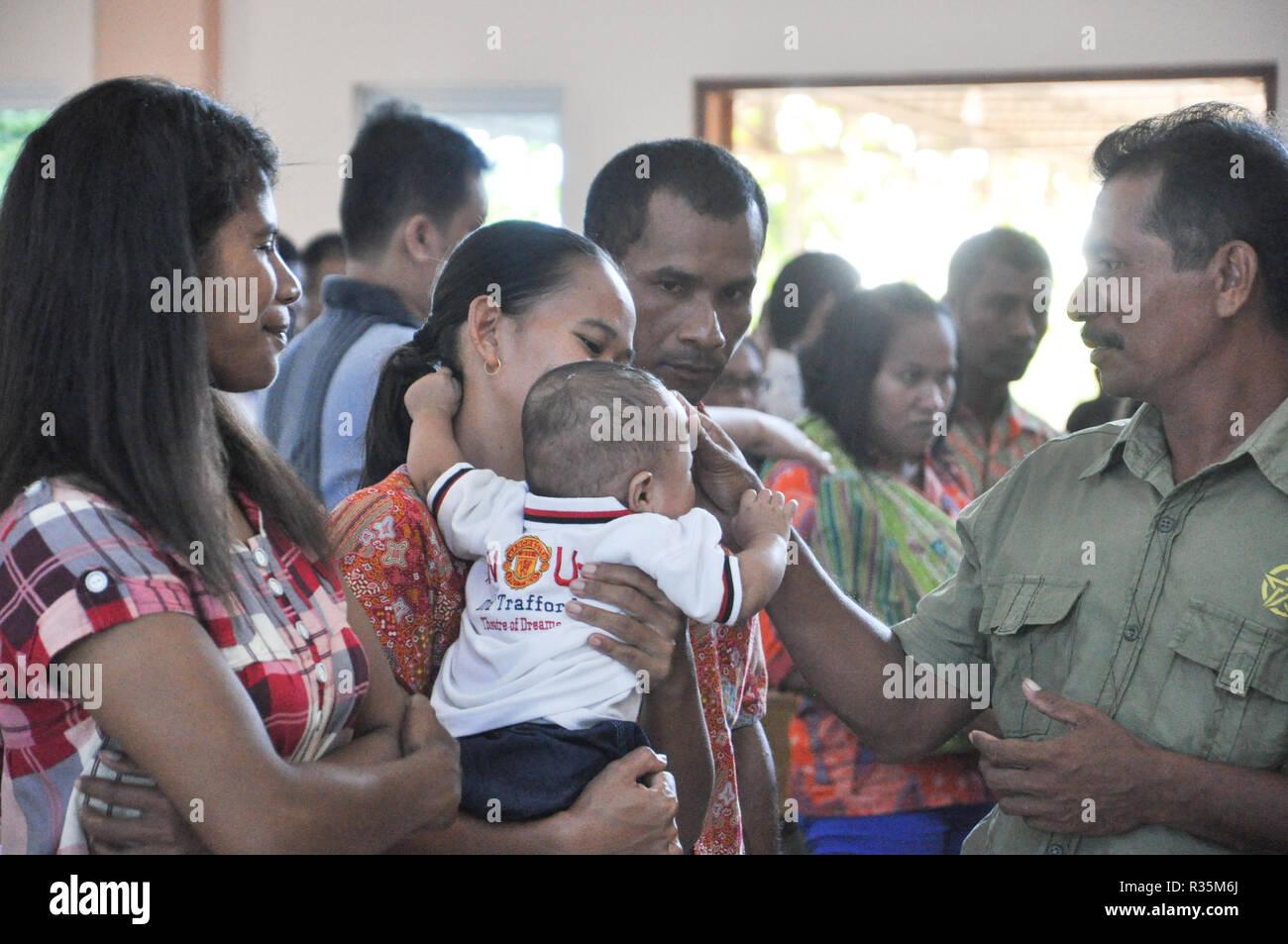 Batam, Indonesia. Families celebrate children baptism. - Stock Image