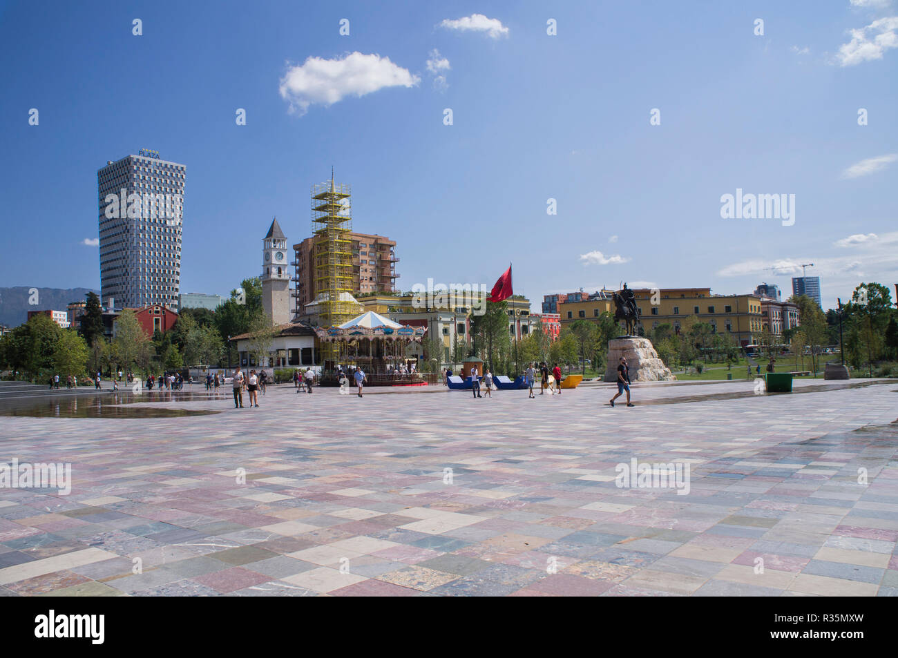 The Plaza Tirana hotel, Clock Tower, Hadji Et'hem Bey Mosque, old-fashioned style carousel, Skanderbeg equestrian statue in Skanderbeg Square in Tiran - Stock Image