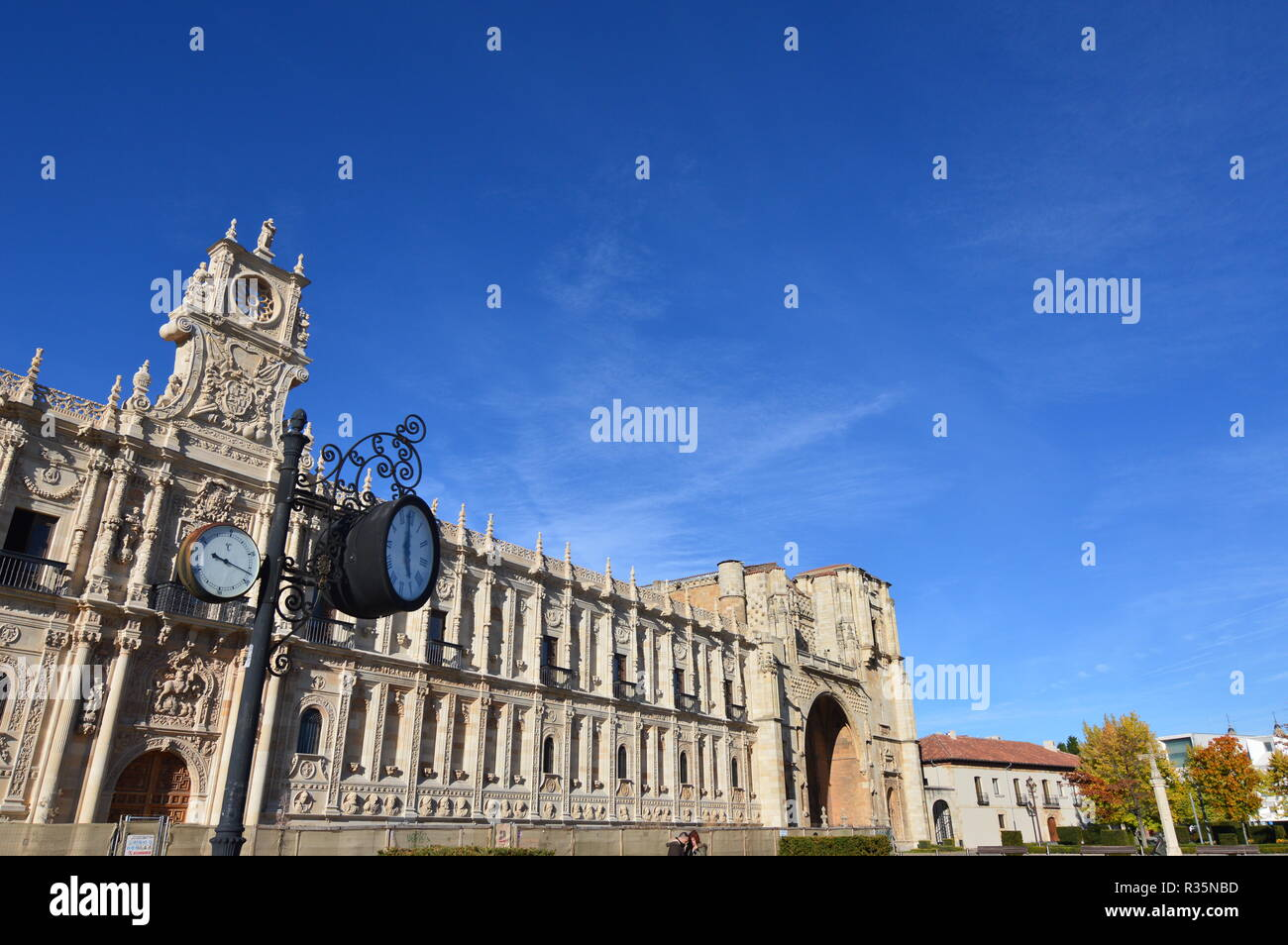 Main facade of the old convent and Hospital San Marcos with a clock and an Analog Thermometer in the foreground in León. Architecture, travel, history - Stock Image