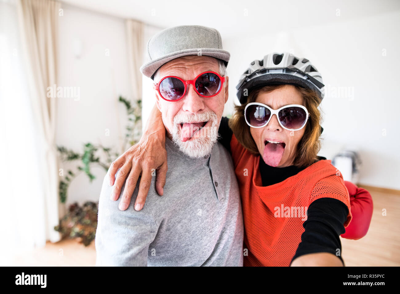 a86aa379 A senior couple with sunglasses having fun at home. - Stock Image