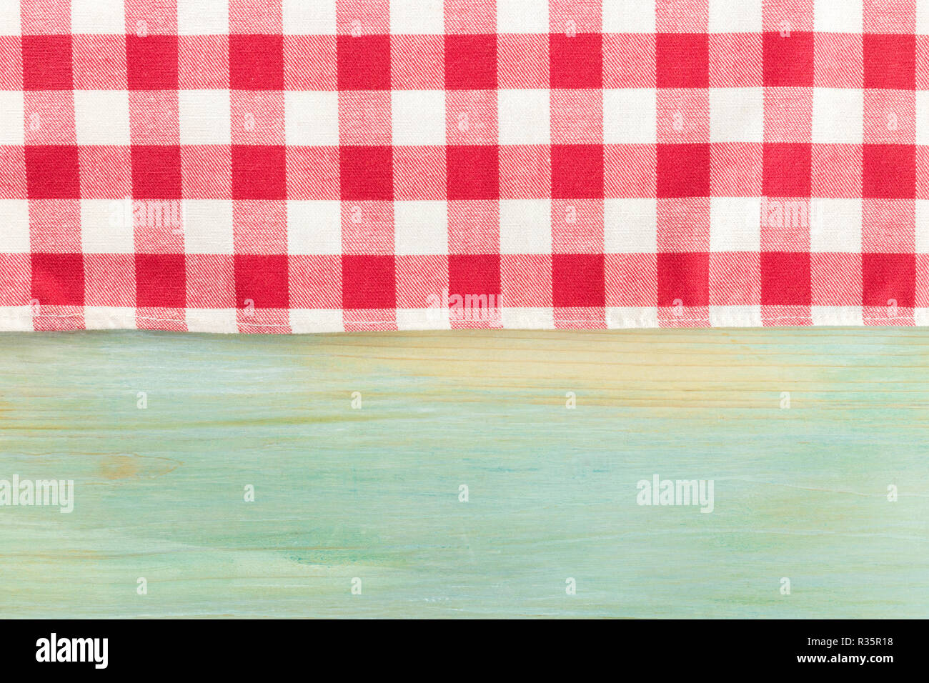 A photo of a gingham cloth on a teal background, an abstract restaurant frame with a place for text - Stock Image