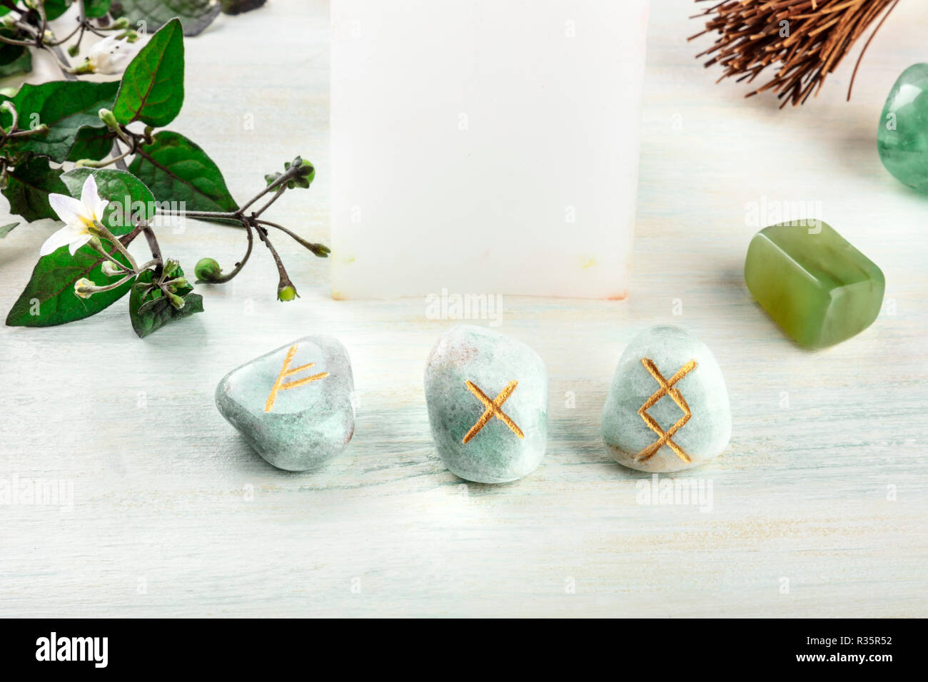 Norse runes, stones with symbols used in Wicca and other magic and for divination, with a candle and crystals with a place for text - Stock Image