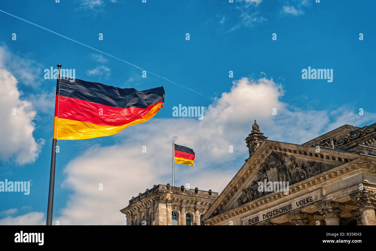 German flags waving in the wind at famous Reichstag building, seat of the German Parliament (Deutscher Bundestag), on a sunny day with blue sky and clouds, central Berlin Mitte district, Germany - Stock Image