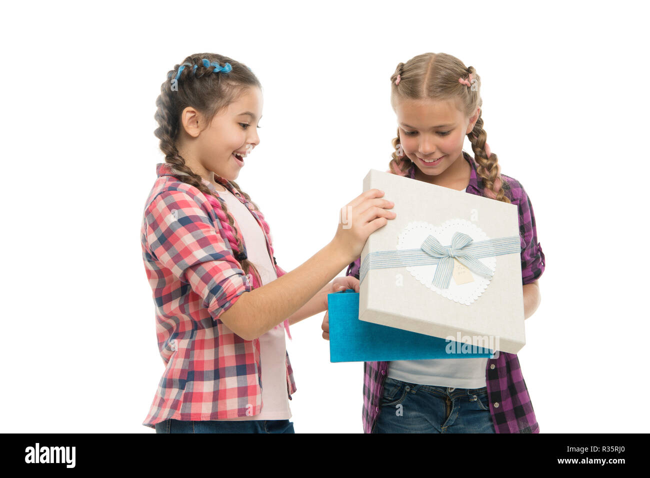 Kids little girls with braids hairstyle hold gift box. Children excited about unpacking gift. Small cute girls sisters received holiday gift. Dreams come true. Best birthday and christmas gifts. - Stock Image