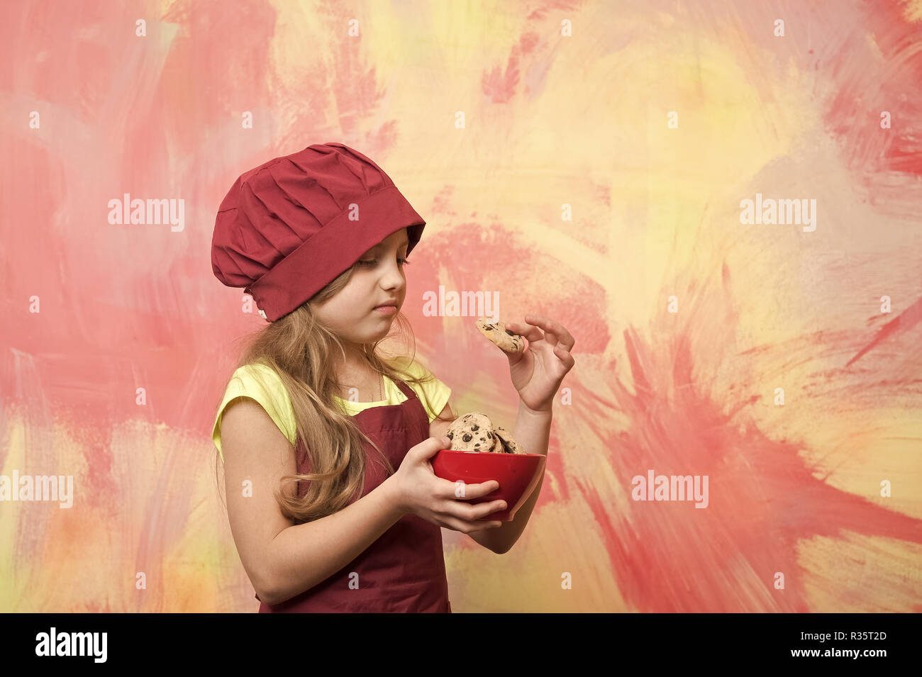 cookies or biscuits in bowl in hand of chef kid or small girl in cook hat and apron with distaste on face on colorful background, copy space - Stock Image