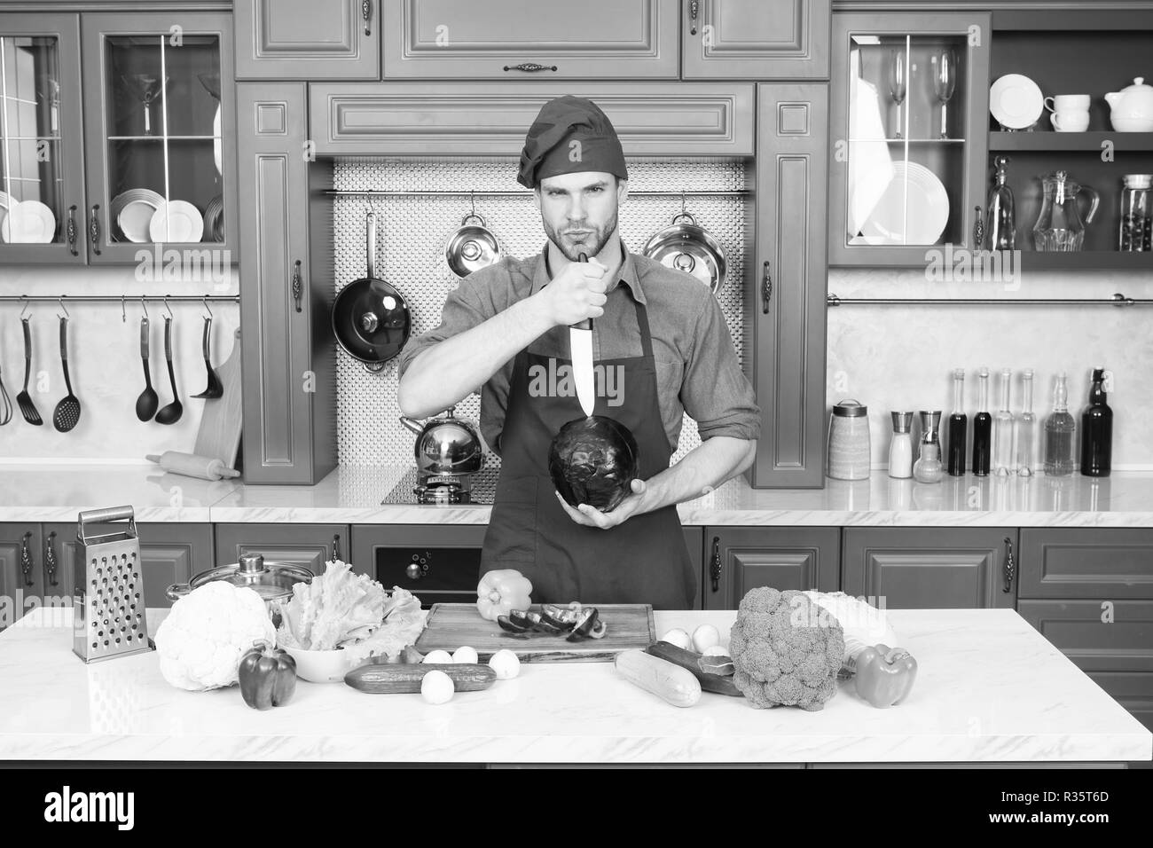 Professional cook. Chef teaches how quickly chop vegetables. Chop food safely and efficiently, ensure that you use the right tools. Learn how hold knife correctly and use right chopping technique. - Stock Image