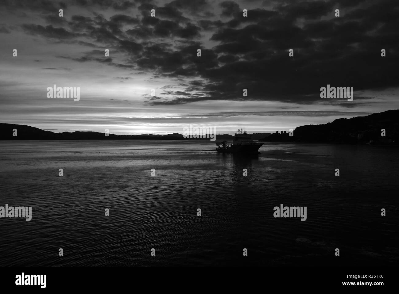 Seascape after sunset in Bergen, Norway. Ship in sea in evening dusk. Dramatic sky over sunset sea water. Traveling with adventures by ship. sunrise. Beauty of nature. Wanderlust and vacation. - Stock Image