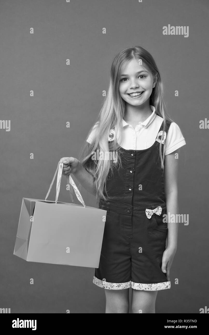 Summer sale. Girl cute teenager carries shopping bag. Kid bought clothing summer sale. Sale benefits. Seasonal sale concept. Girls absolutely fond of shopping. Simple reminders how to shop smart. - Stock Image