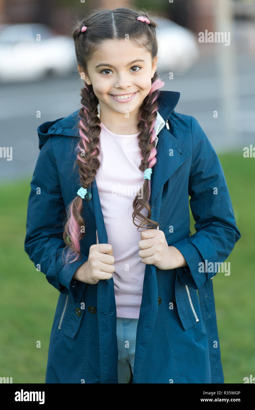 Girl with braided hair style with pink kanekalon. Add bright detail. Little girl with cute braids wear dark coat nature background. Kanekalon strand in braids of cute child. Modern hairstyle concept. - Stock Image