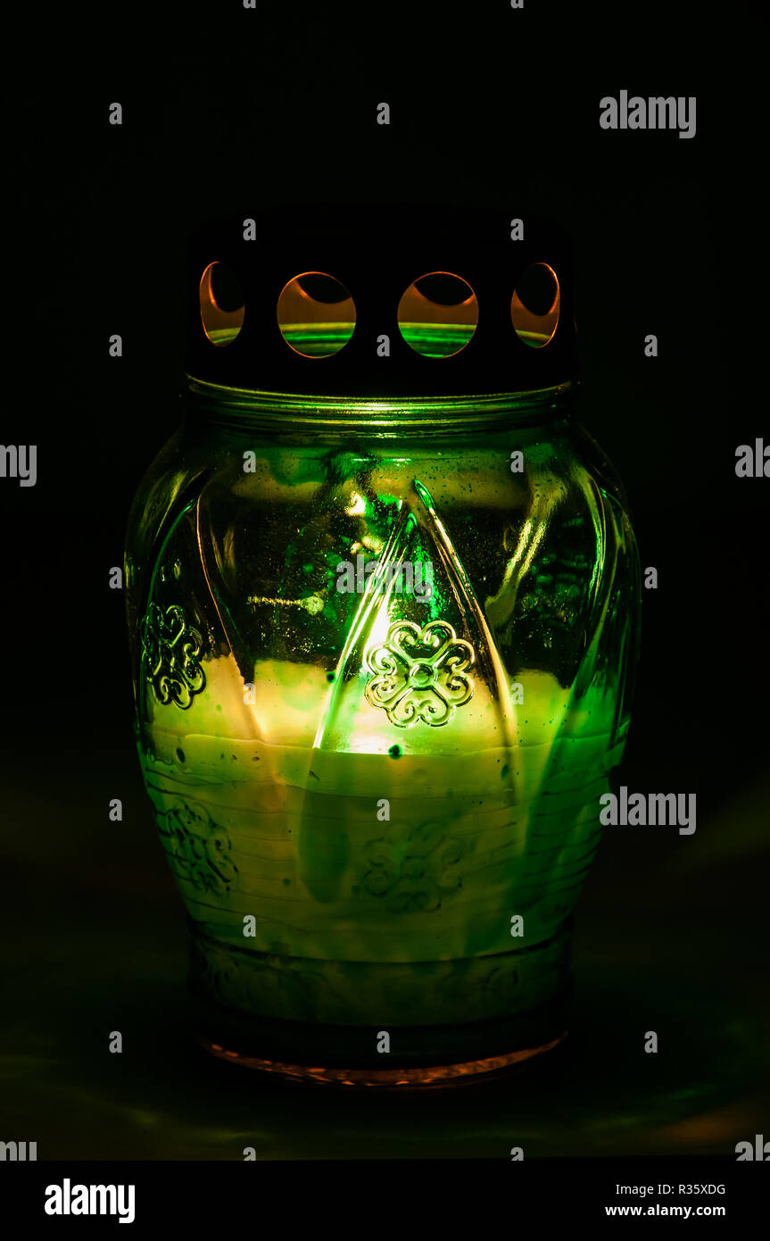 green burning votive candle in the dark - Stock Image