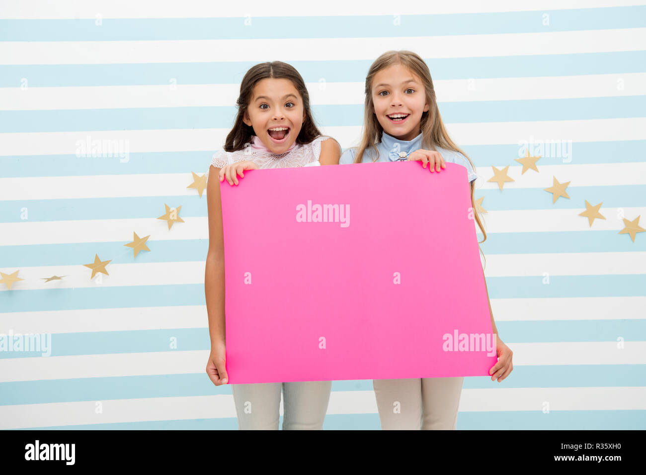 Amazing surprising news. Girl hold announcement banner. Girls kids holding paper banner for announcement. Children happy with blank paper announcement copy space. Kids announcement concept. - Stock Image